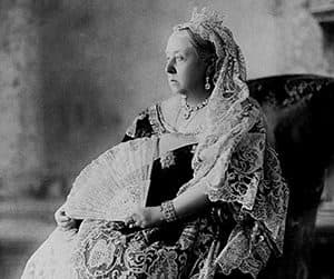 Queen Victoria seated wearing her small diamond crown holding a fan